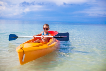 Little adorable girl kayaking in the clear blue sea