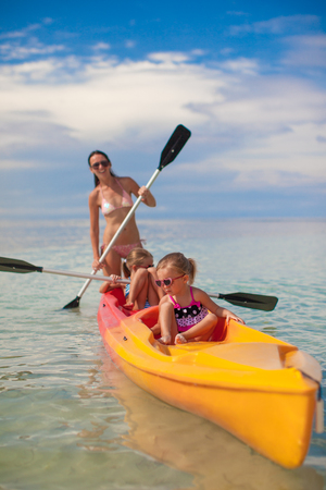 Two little girl and young mother kayaking at blue warm sea photo