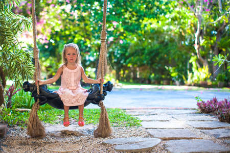 Beautiful little girl swinging on a swing in a cozy lovely flowered courtyard photo