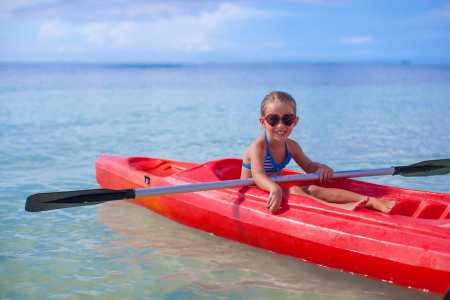 Little brave cute girl floating in a kayak on the high blue sea photo