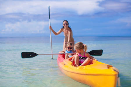 Two little girl and beautiful mother kayaking at tropical warm sea photo