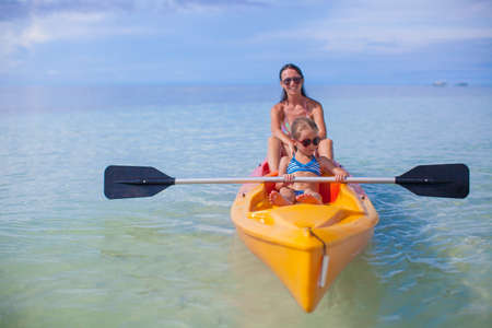 Two kids with their mom in a boat floating in the clear sea photo