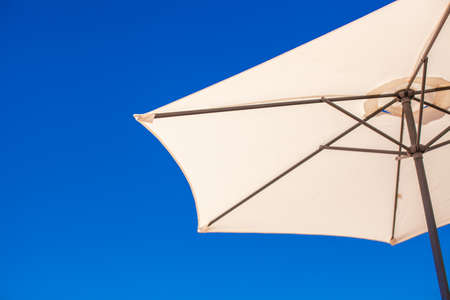 Part of white umbrella on background blue sky at the beach photo