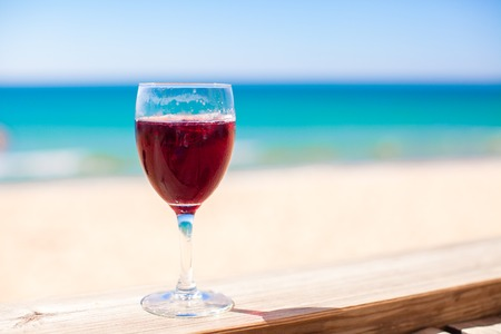Glass of red wine against the turquoise sea photo