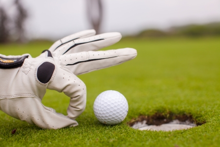Golf player man pushing golf ball into the hole Stock Photo
