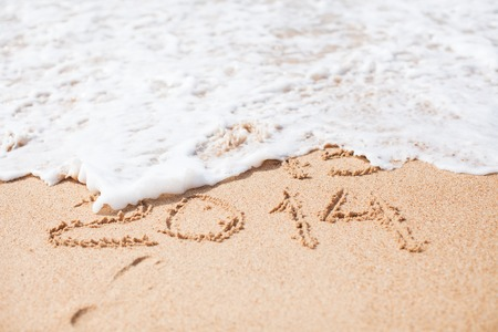 Year 2014 written in sand on tropical beach photo