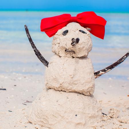 Little sandy snowman with bow on white Caribbean beach photo