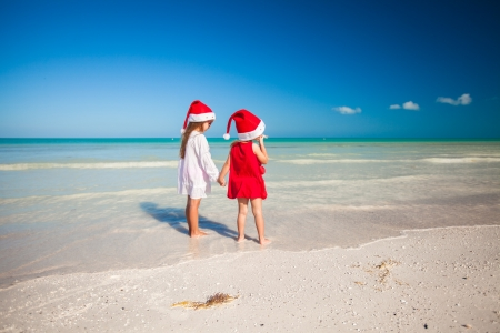 Rear view of Little cute girls�in Christmas hats on the exotic beach photo