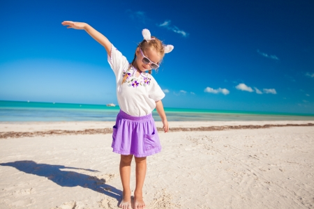 Adorable little girl in easter costume on the exotic beach photo