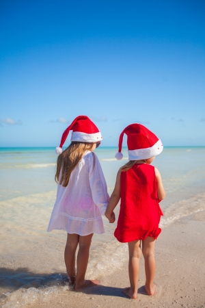 Back view of Little cute girls�in Christmas hats on the exotic beach photo