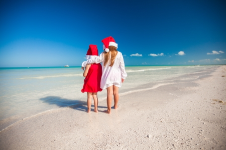 Two little cute girls�in Christmas hats have fun on the exotic beach photo