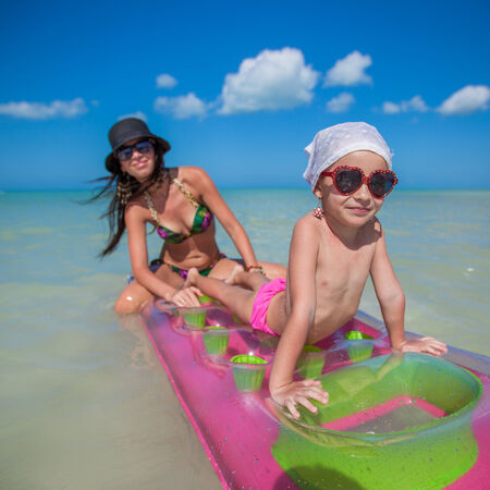 Little girl with young mother on an air mattress in the sea photo
