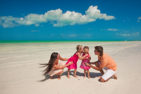 Young beautiful family with two daughters having fun at beach photo