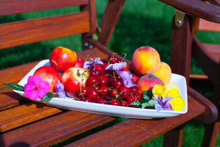 Plate with fresh fruits and flowers on wooden chairs in the garden photo