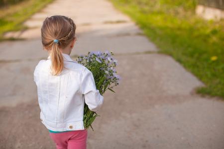 Petite fille mignonne marche avec un bouquet de fleurs Banque d'images - 24341792