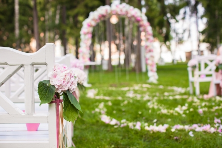 entrance arbor: Wedding benches and flower arch for a wedding ceremony outdoors