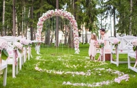 feier: Hochzeits-Bänke mit Gästen und Blumenbogen für die Zeremonie im Freien