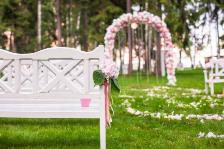Wedding benches and flower arch for a wedding ceremony outdoors photo