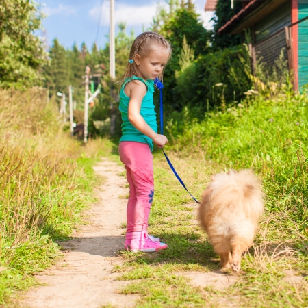 Little girl walking with her dog on a leash photo
