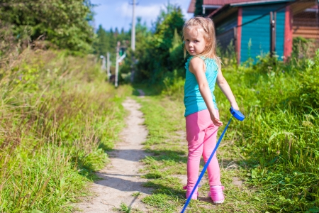 Little girl walking with her ​​dog on a leash photo