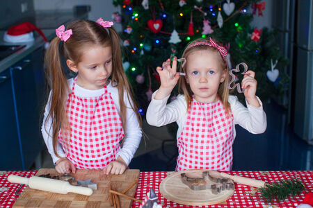 Cute little girls baking ginger cookies for Christmas at kitchen photo