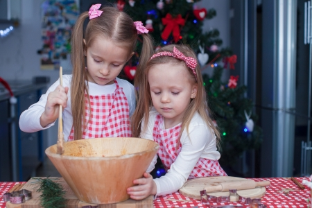 christmas baker's: Little cute sisters bake gingerbread cookies for Christmas