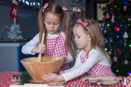 Cute little girls preparing gingerbread cookies for Christmas photo