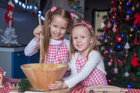 Two little girls make gingerbread cookies for Christmas photo