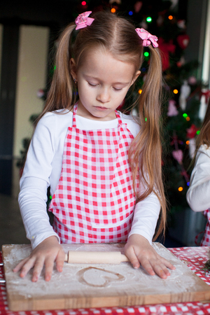 Little girl baking gingerbread cookies for Christmas at home photo
