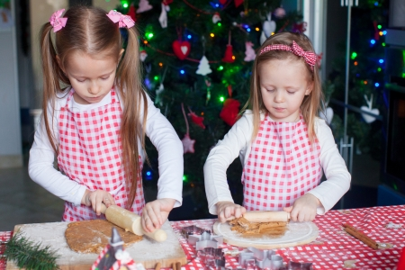Two little adorable girls make gingerbread cookies for Christmas photo