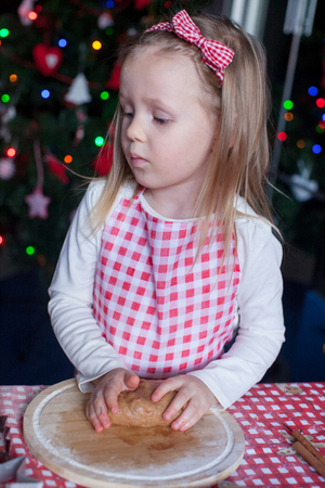 Adorable little girl baking gingerbread cookies for Christmas at kitchen photo