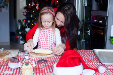 Little girl with beautiful mother baking Christmas gingerbread cookies together photo
