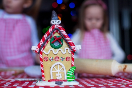 Gingerbread fairy house decorated by colorful candies on a background of little girls photo