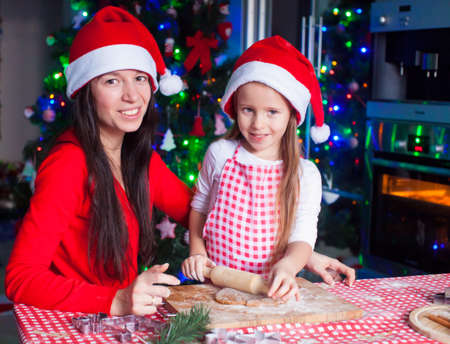 Happy mom and little girl baking Christmas gingerbread cookies together photo