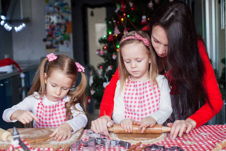 Young mother with little cute girls bake Christmas gingerbread cookies photo