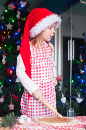 Adorable little girl with rolling pin baking gingerbread cookies for Christmas photo