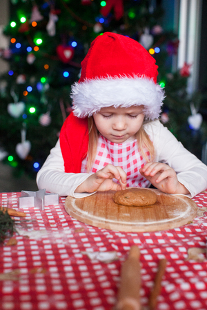 Little girl in Santa hat baking gingerbread Christmas cookies photo