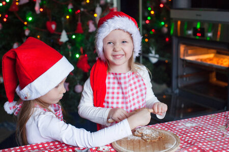 Little girls baking gingerbread cookies for Christmas in Santa hat photo