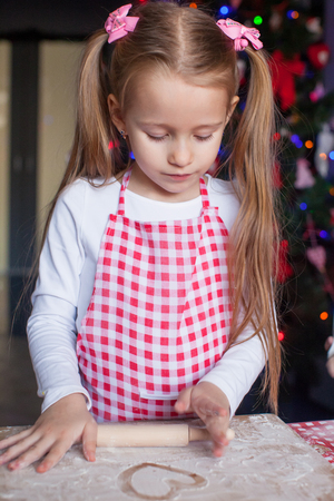 Little happy girl with rolling pin baking gingerbread cookies for Christmas photo