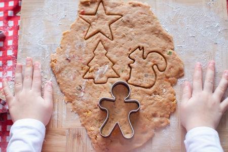 Child hands making from dough gingerbread man for Christmas photo