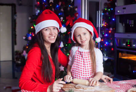 Adorable girl with her mother baking Christmas cookies in the kitchen photo