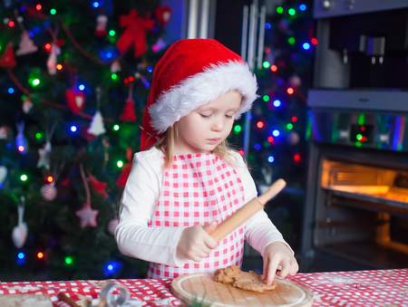 Adorable little girl in Santa hat  baking gingerbread Christmas cookies at home photo