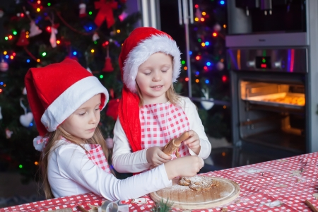 Cute little girls preparing gingerbread Christmas cookies in the kitchen photo
