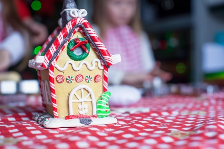 Gingerbread fairy house decorated by colorful candies on a little girl photo