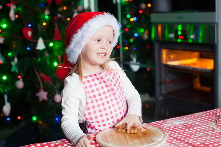 Happy cute little girl in the kitchen baking gingerbread photo