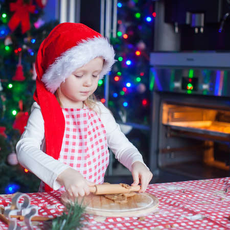 Portrait of little girl with rolling pin baking Christmas gingerbread cookies photo