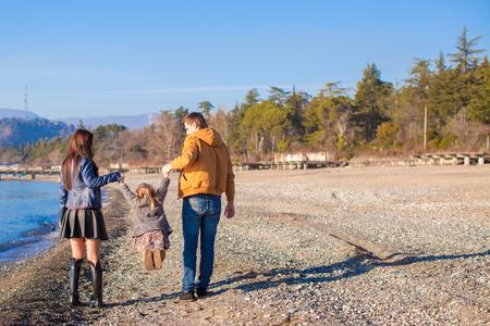 Family of three have fun near the Black Sea in winter sunny day Stock Photo