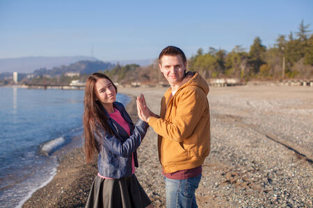 Happy couple having fun at the beach on a sunny fall day photo