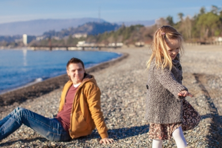 Adorable little girl with father having fun on beach in winter warm day photo