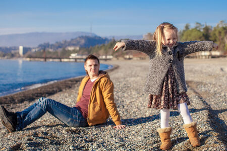 Young father and his little adorable daughter having fun on winter beach photo